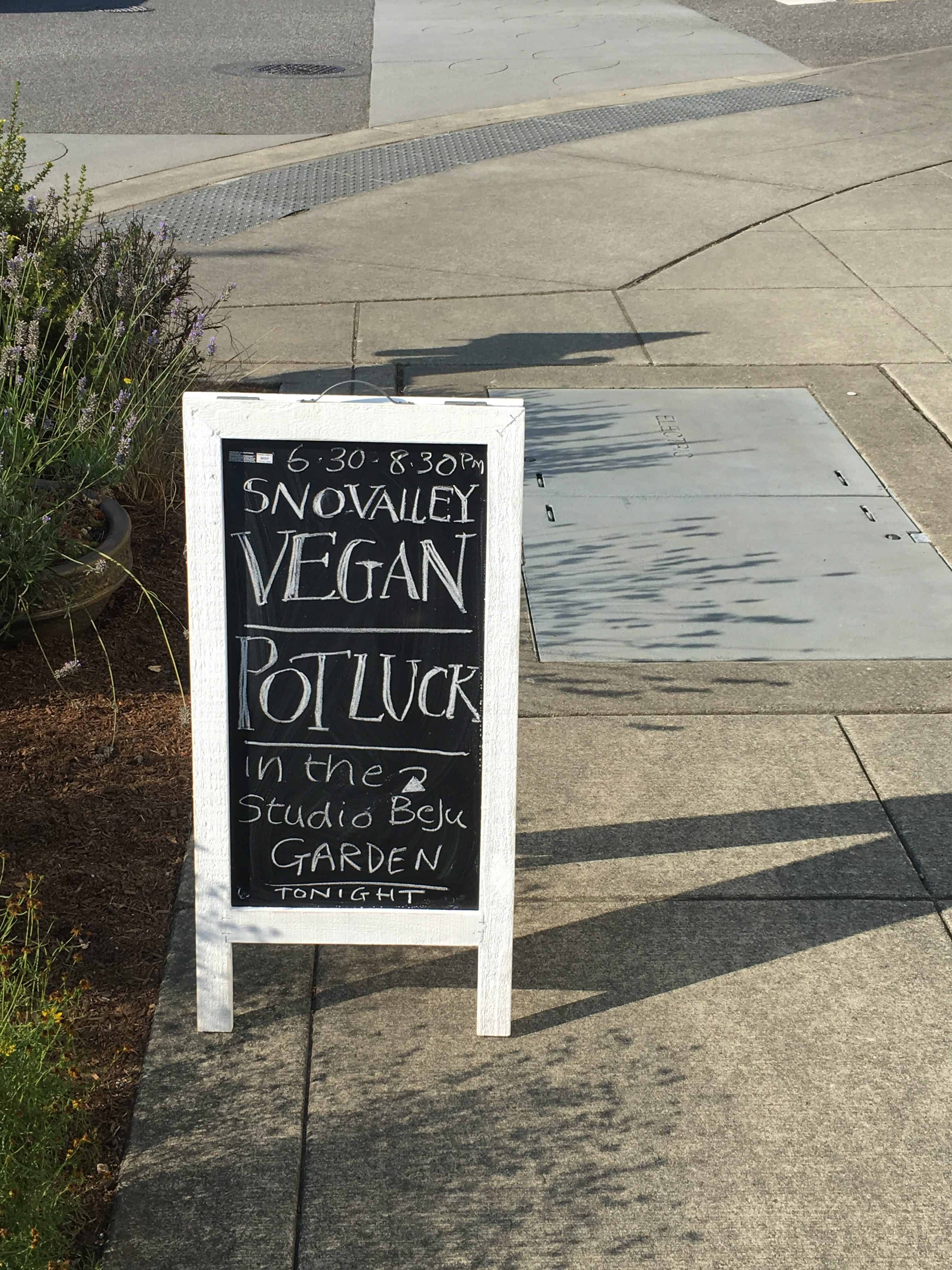 Photo of an A-Board sign on a sidewalk indicating the Sno-Valley Vegan Potluck in the Studio Beju garden. https://trimazing.com