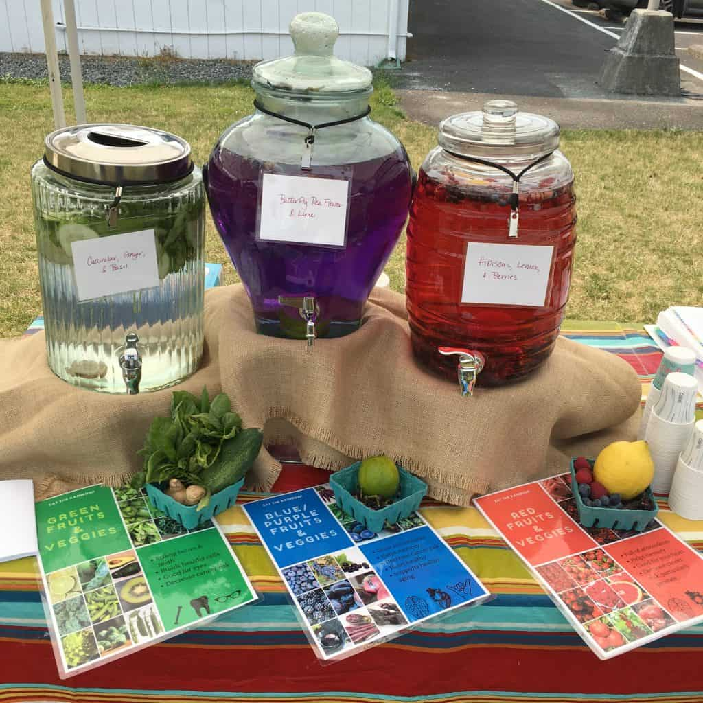 Photo of three infused water dispensers at the Carnation Farmers Market Power of Produce Kids Club, Summer 2018. Includes: Cucumber, Basil, Ginger (left), Butterfly Pea Flower and Lemon (center), and Hibiscus, Lemon, and Berries (right). https://trimazing.com/