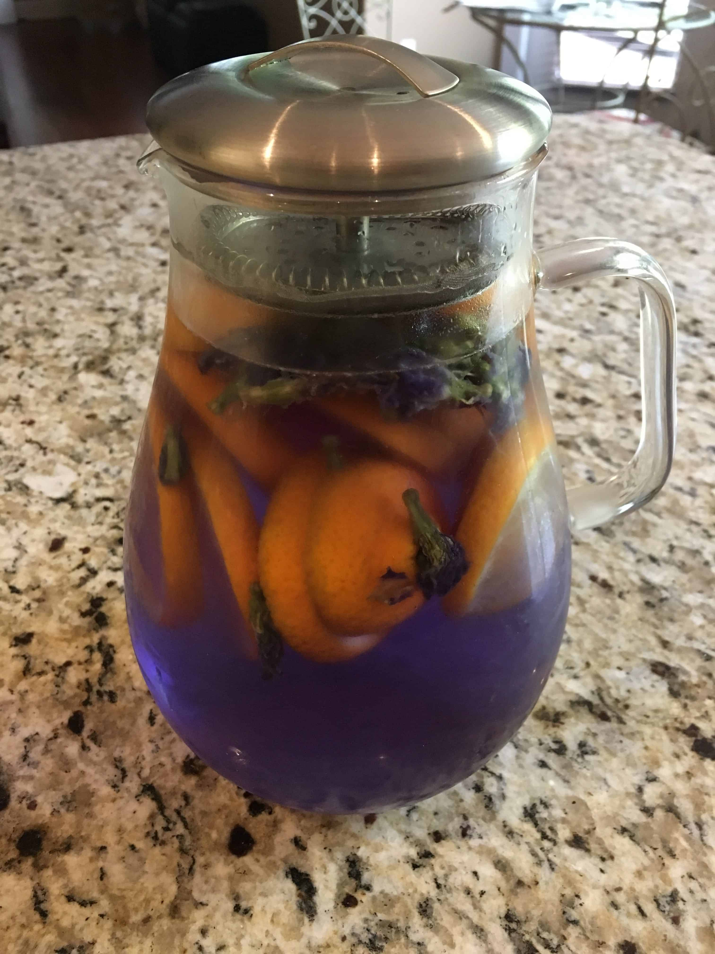 Photo of an Infusion Pitcher with Metal Screen to keep contents from pouring out. Pitcher contains Butterfly Pea Flowers and Lemons. https://trimazing.com/