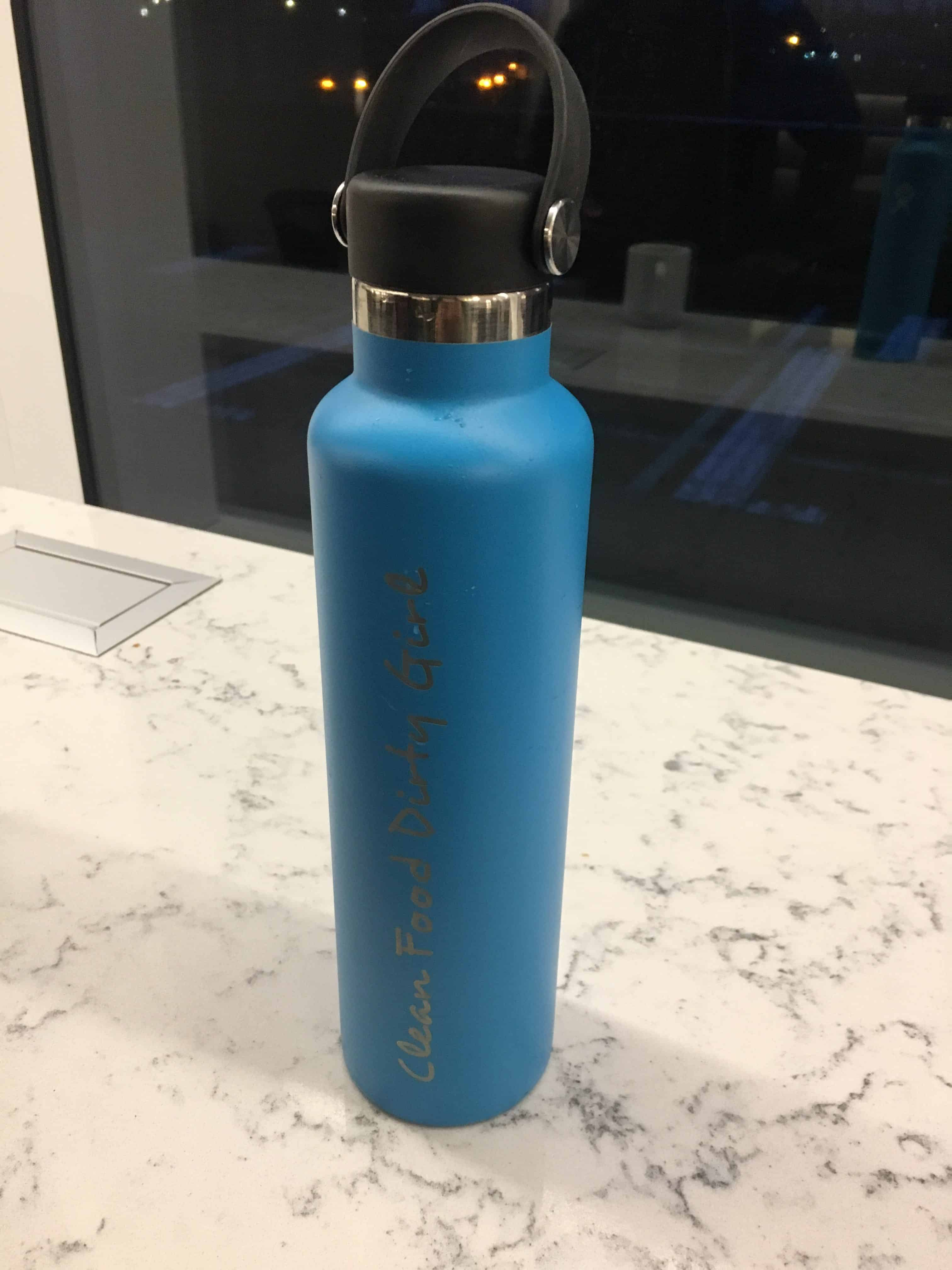 Photo blue Hydroflask stainless steel water bottle embossed with Clean Food Dirty Girl on marble counter of the United Club in SeaTac airport. https://trimazing.com/