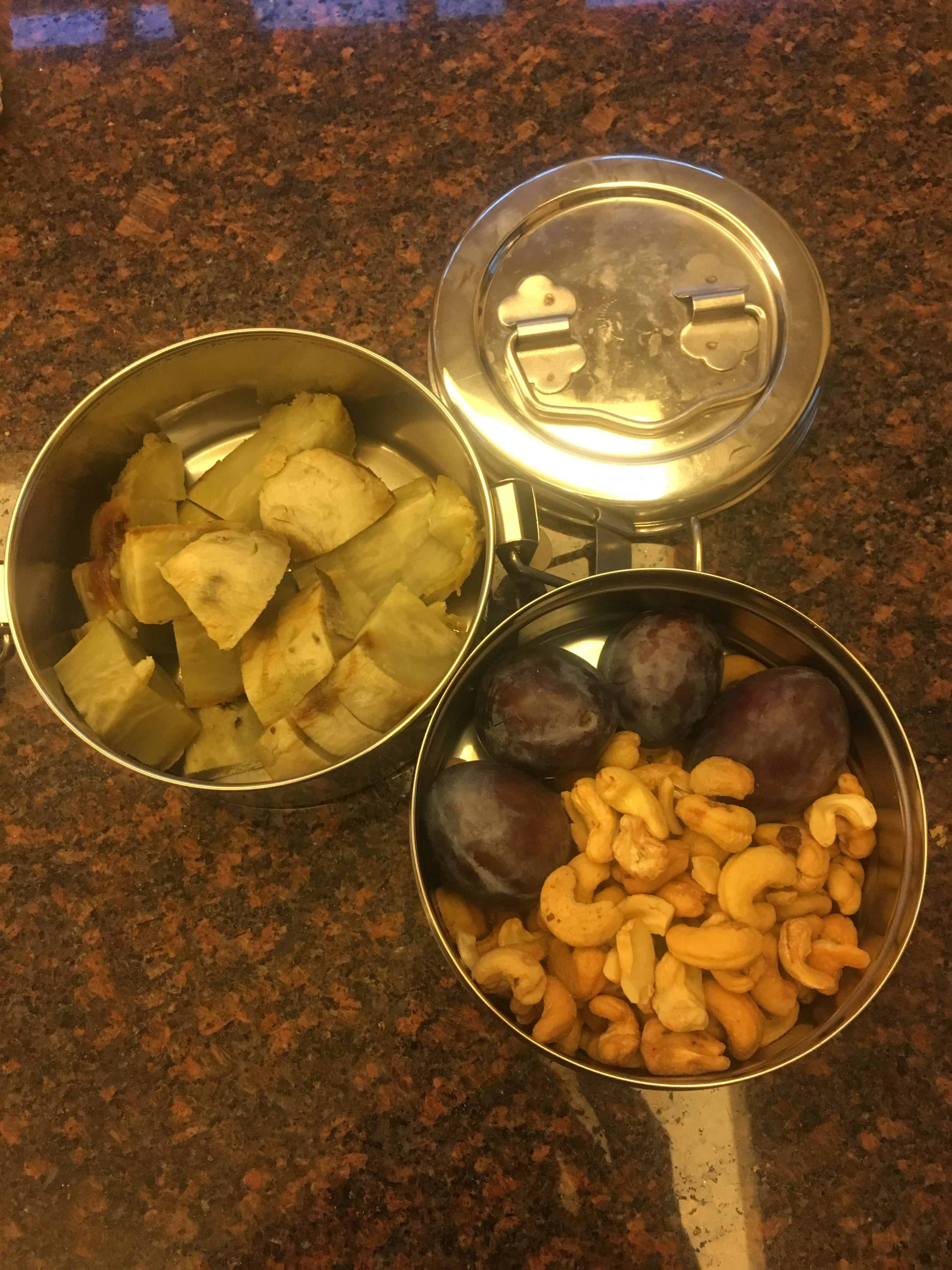 Photo of two tiffin sections, one with roasted cashews and Italian plums, another with cubed cooked sweet potato. https://trimazing.com/