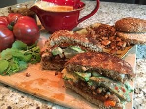 Photo of finished Cemita Torta, cut in half, with ingredients for used to make it, including (clockwise from top left) heirloom tomato, adobo, Mexican queso, Mexican jackfruit, and Ezekiel bun, on a bamboo cutting board. https://trimazing.com/
